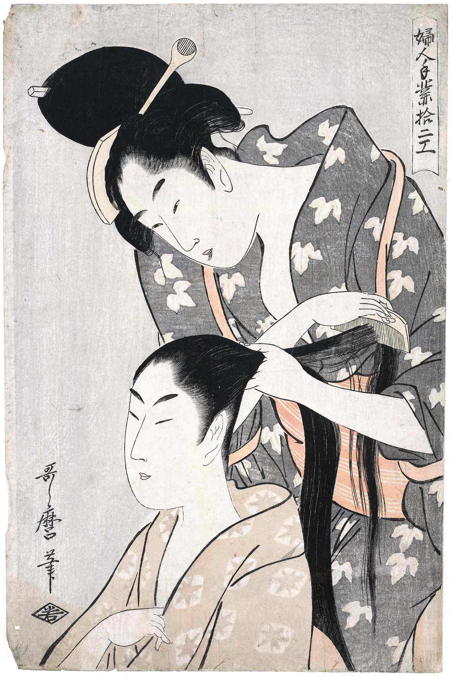 A woman combs the hair of another woman.