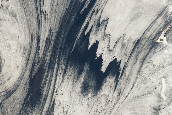Dark streaks of ash embedded in Skeiðarárjökull, a glacier in Iceland.