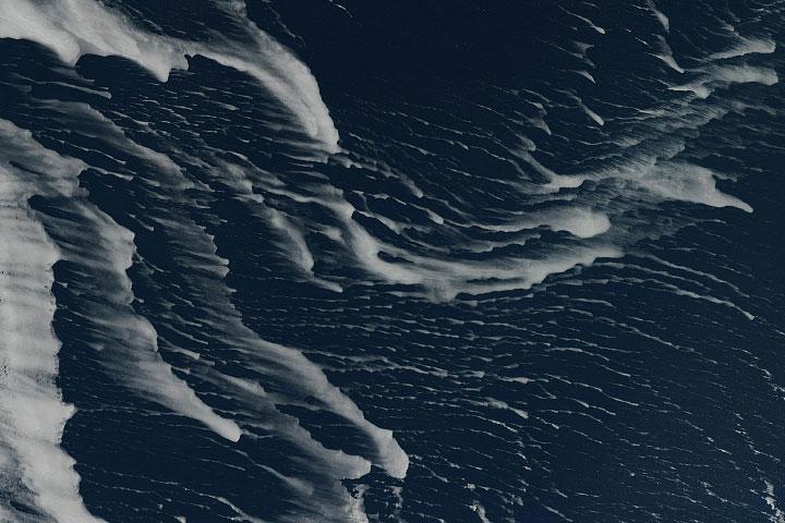Drift ice appear as thin white streaks in the dark blue Sea of Okhotsk.